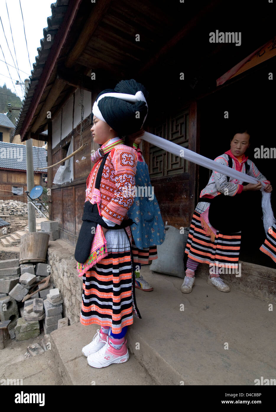 A Long Horn Miao teenage girl getting ready for the Tiao Hua festival in Guizhou. - Stock Image