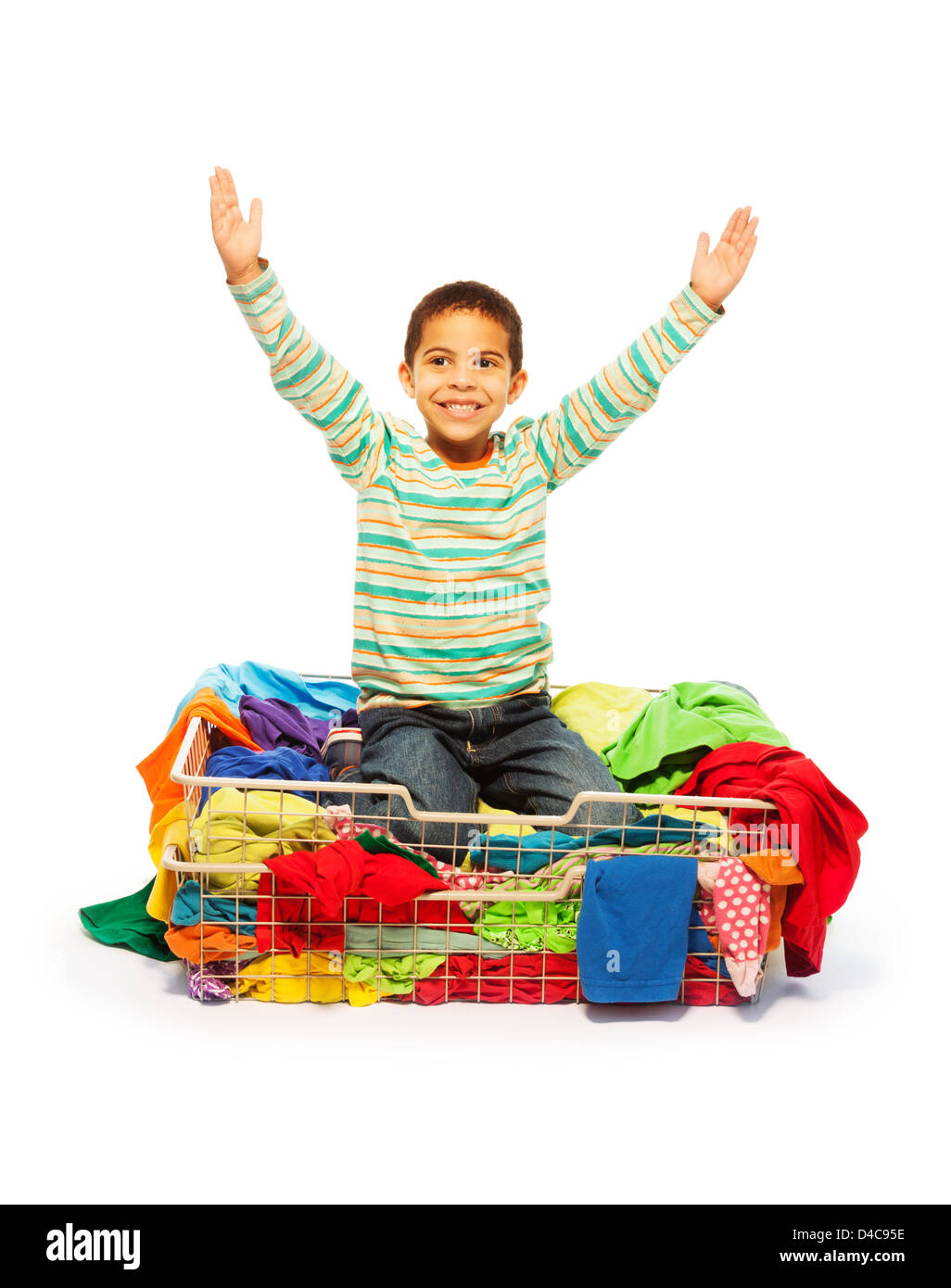 Cute five years old black boy sitting in basket with fashion clothes and his hands lifted, isolated on white - Stock Image