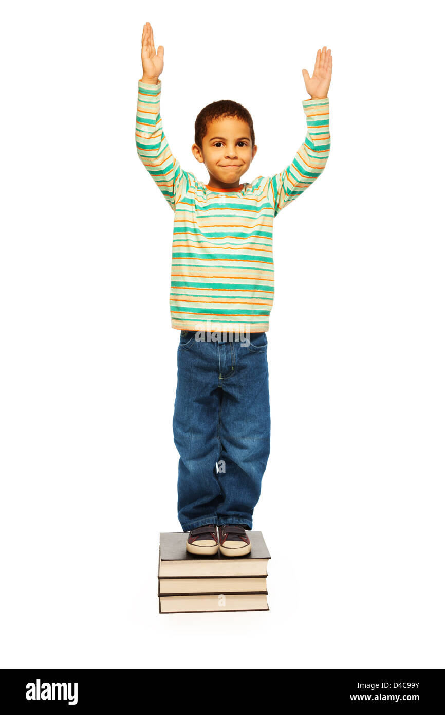 Black clever cute looking boy with smile on face standing on pile books - Stock Image
