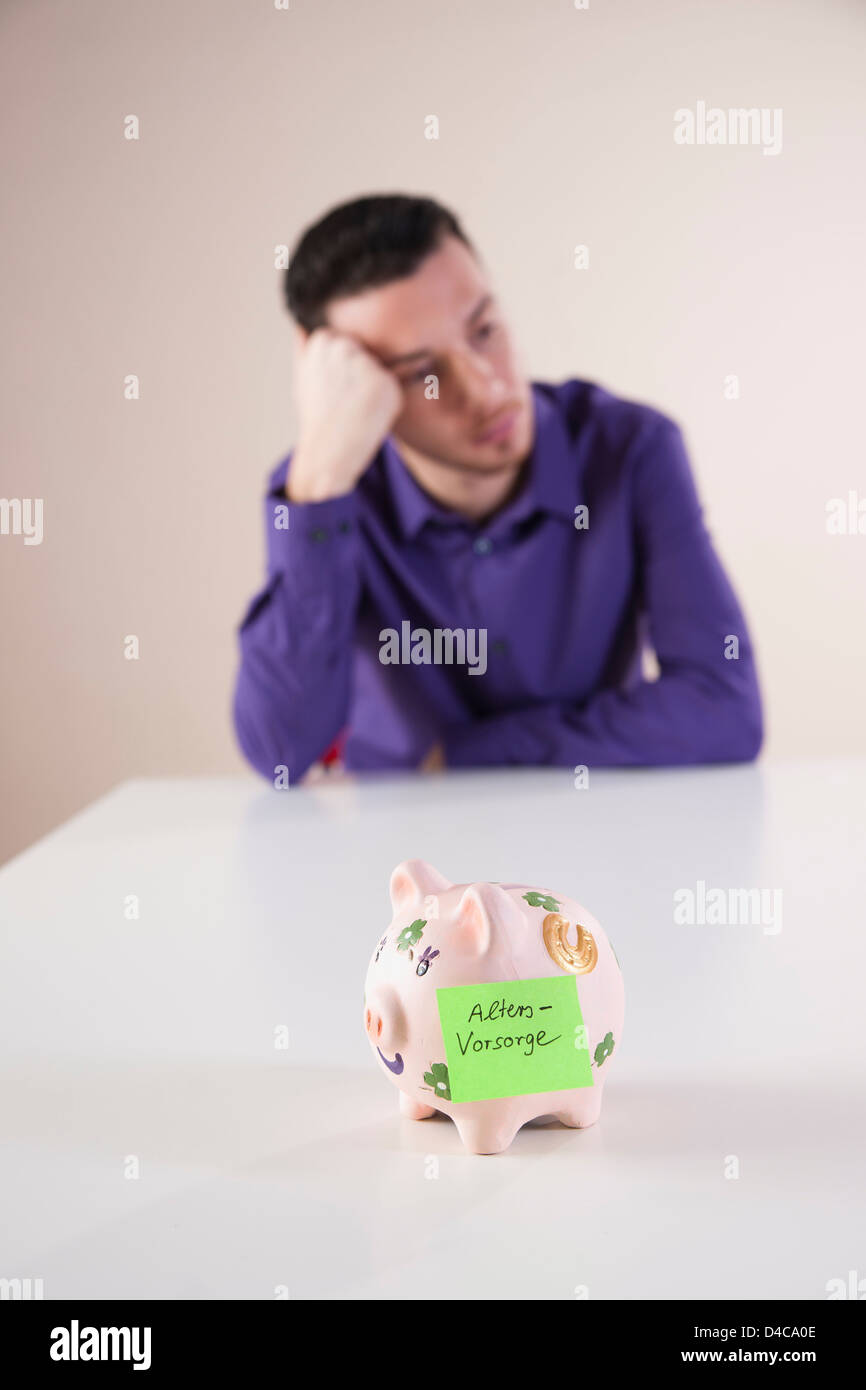 Serious young man with piggy bank for pension plan - Stock Image