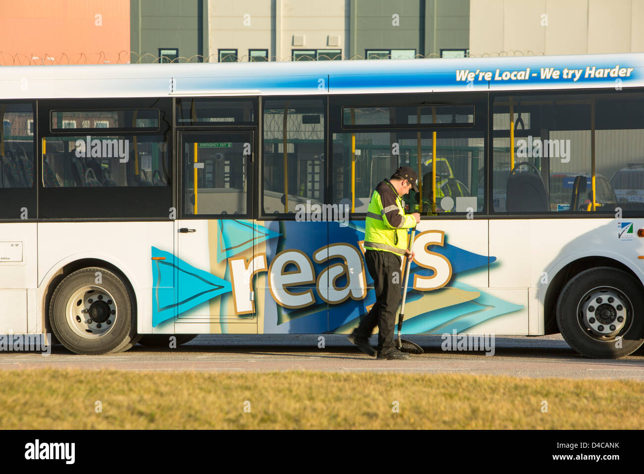 A security guard uses a mirror to checks the underside of a coach for bombs before it enters Sellafield nuclear - Stock Image