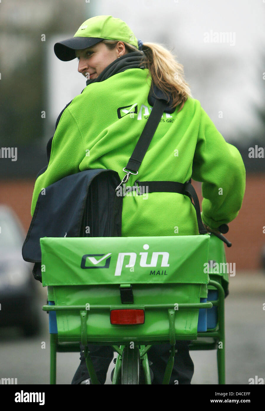 A female mployee of postal service provider  PIN drives on her bicycle in Cologne, Germany, 23 January 2008. Nineteen - Stock Image