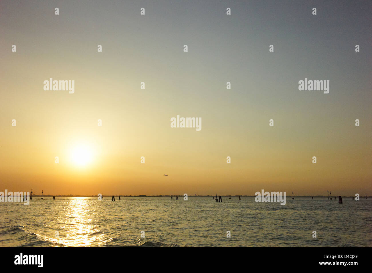 A distant plane flies over the Venice Lagoon in Venice, Italy at sunset - Stock Image