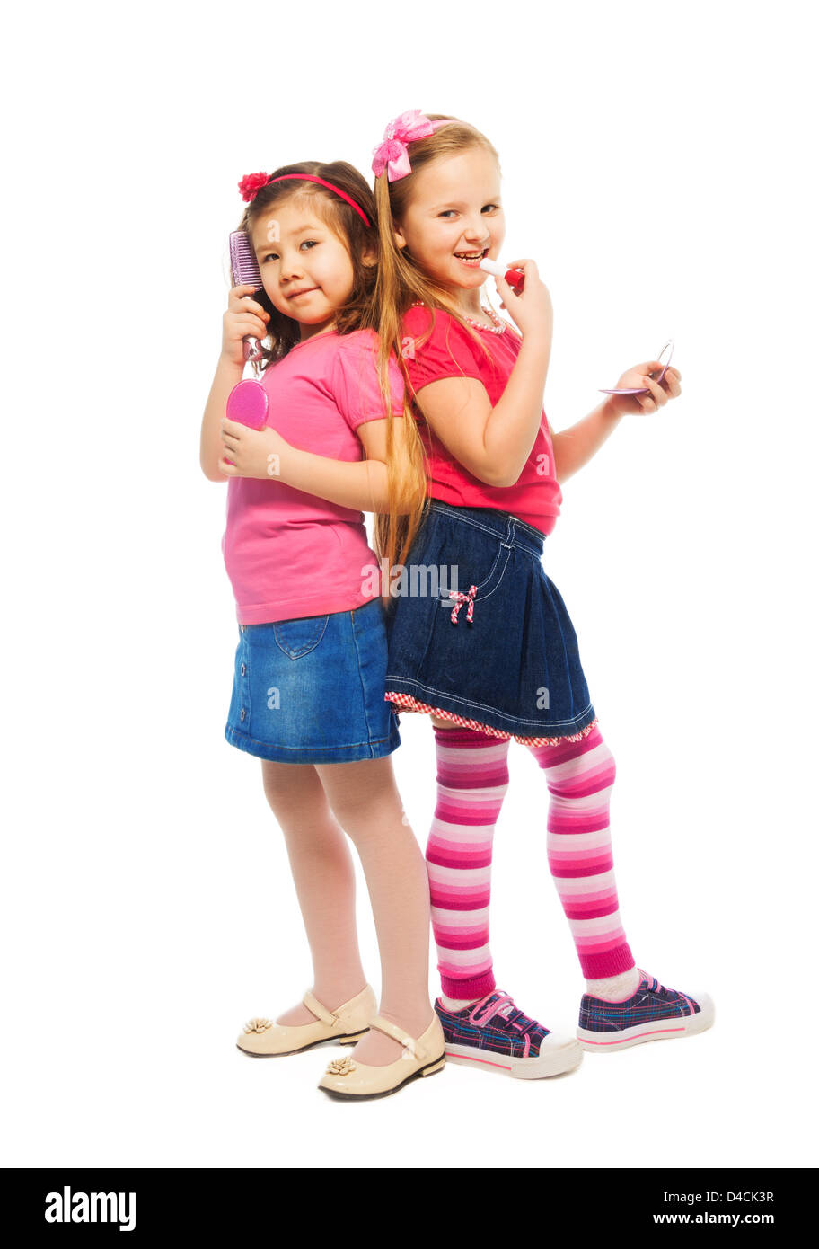 Two girls Caucasian and Asian playing to be big like mother brushing and making up face, isolated on white, full - Stock Image