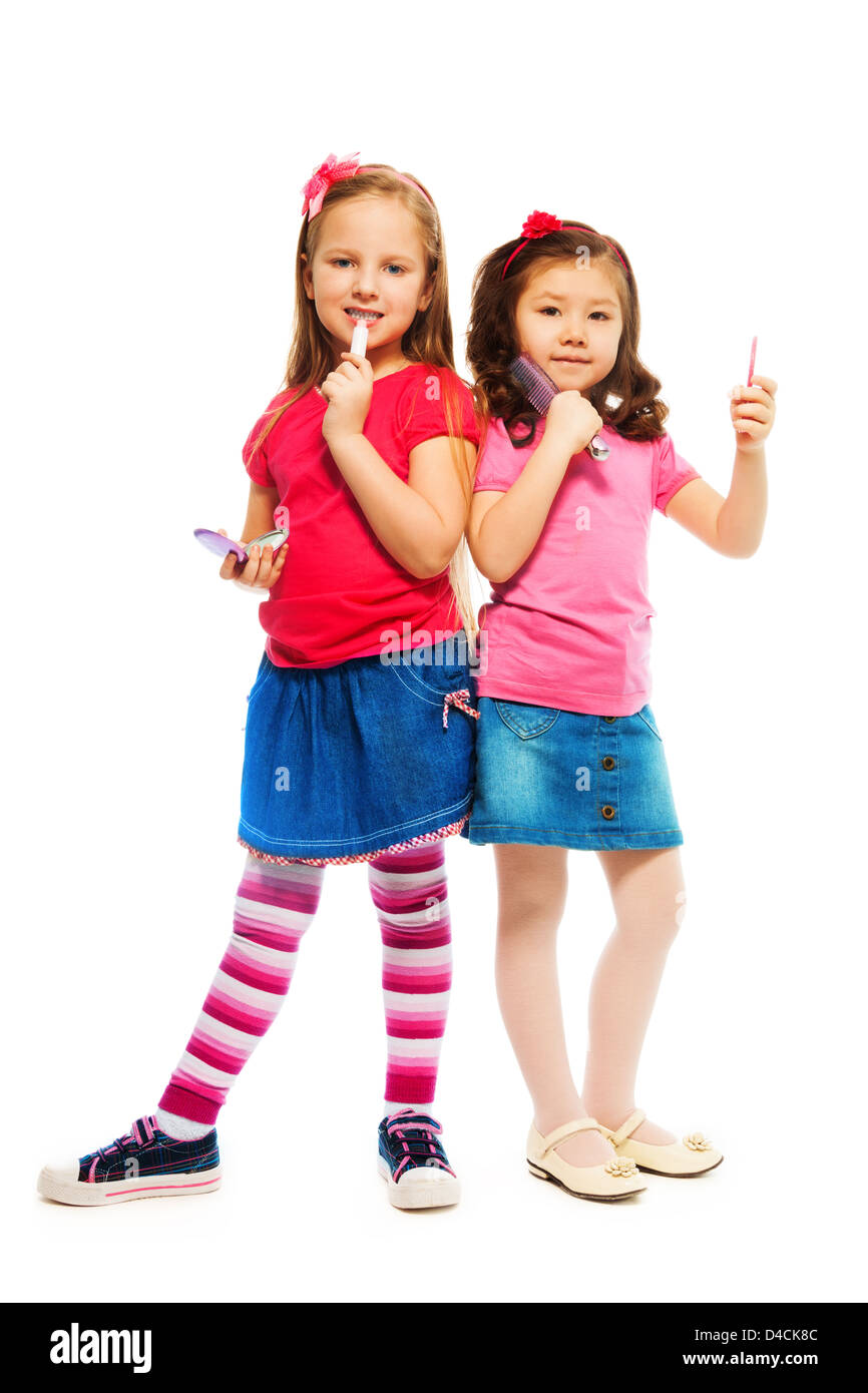 Two girls Caucasian and Asian playing to be big like older sisters brushing and making up face, isolated on white, - Stock Image