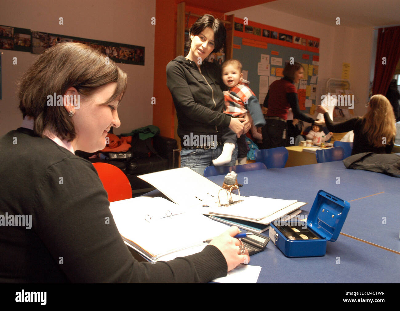 Voluntary worker Izmira Dervisoska (L) talks to young mother Jasmin Akcagear with her son Daniel in the multigenerational Stock Photo