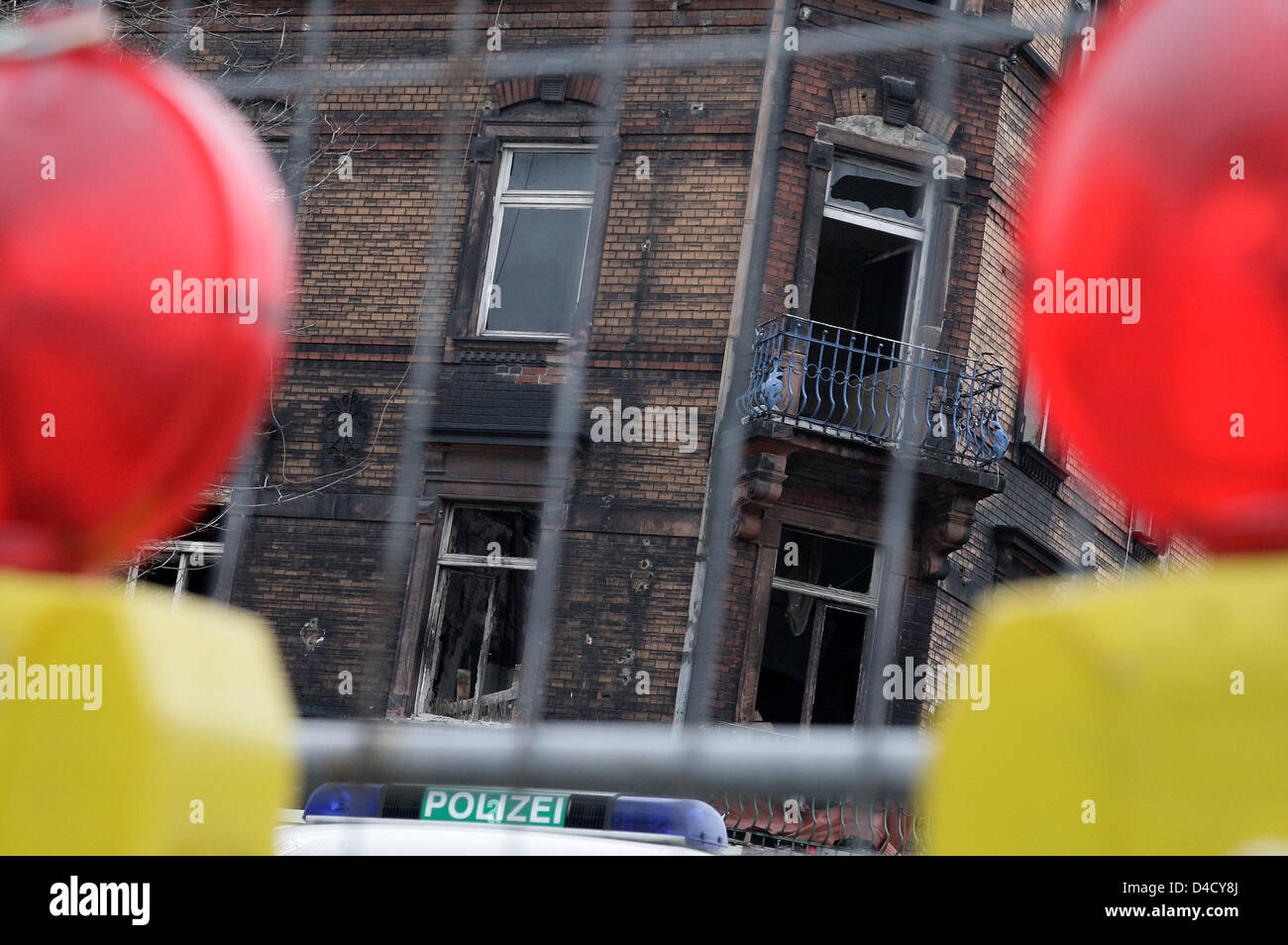 Red lights of a police barrier frame the burnt-out residential house ...