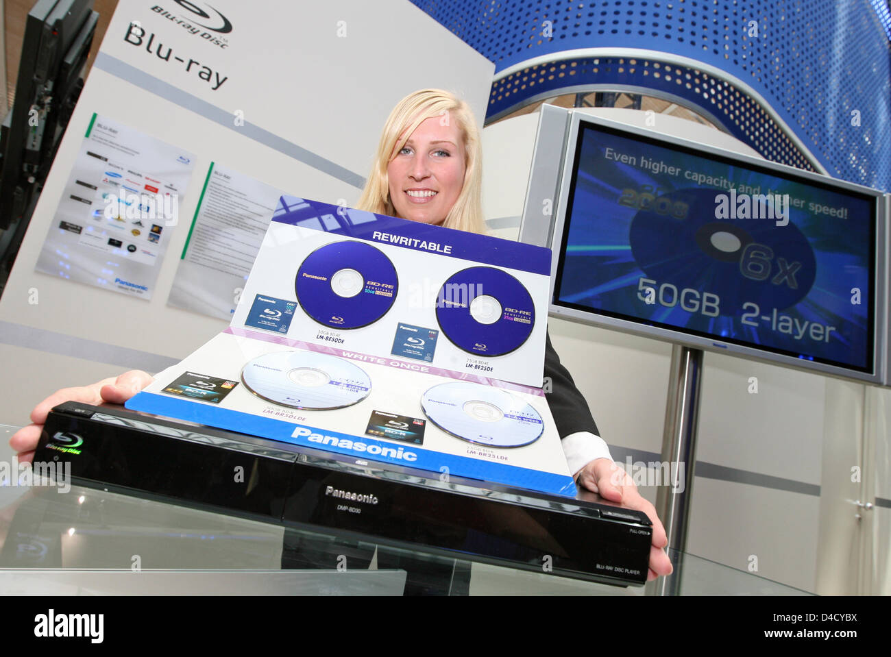Model Julia presents a Panasonic DMP-BD 30 Blu-ray Disc player (bottom) and various rewritable Blu-ray discs at - Stock Image