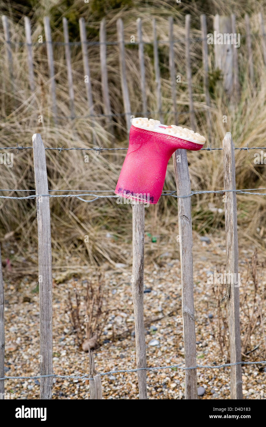 Lost red child's wellington boot on fence post, Dunwich, Suffolk, England - Stock Image