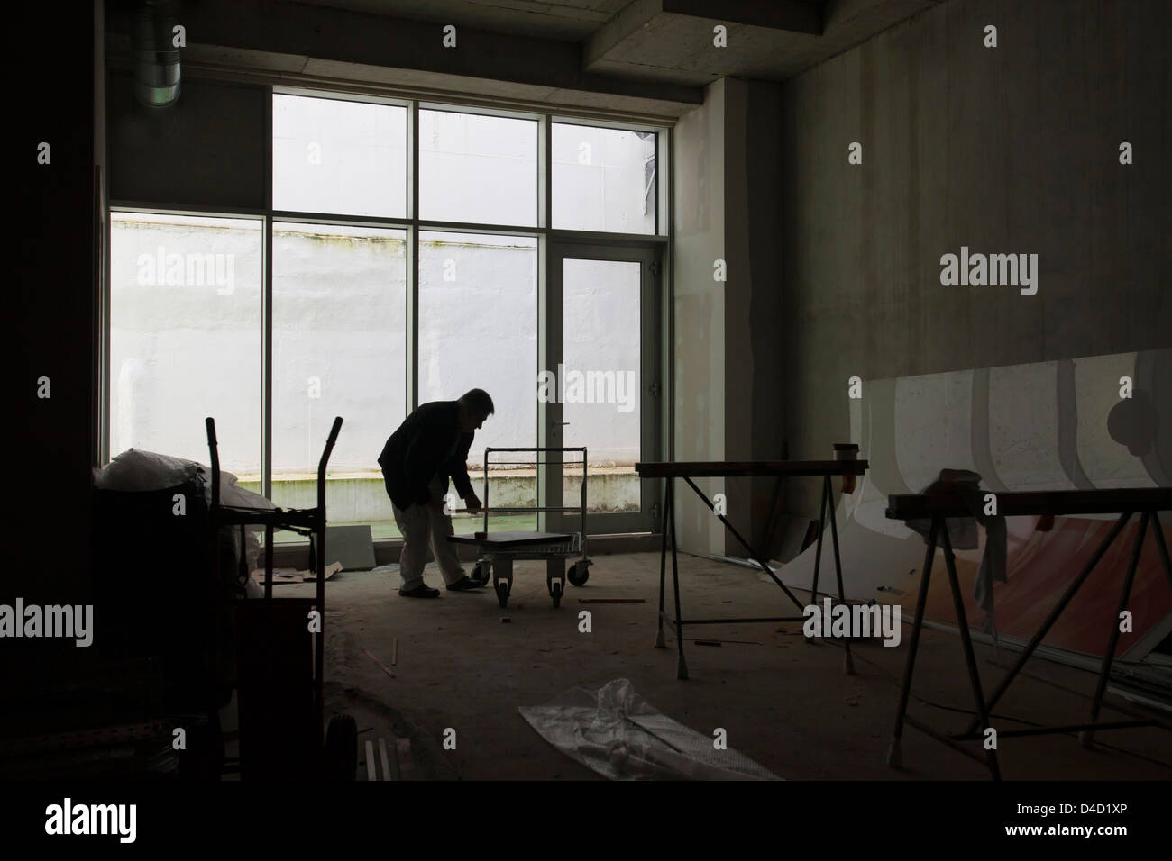 Silhouette of construction worker inside building. - Stock Image