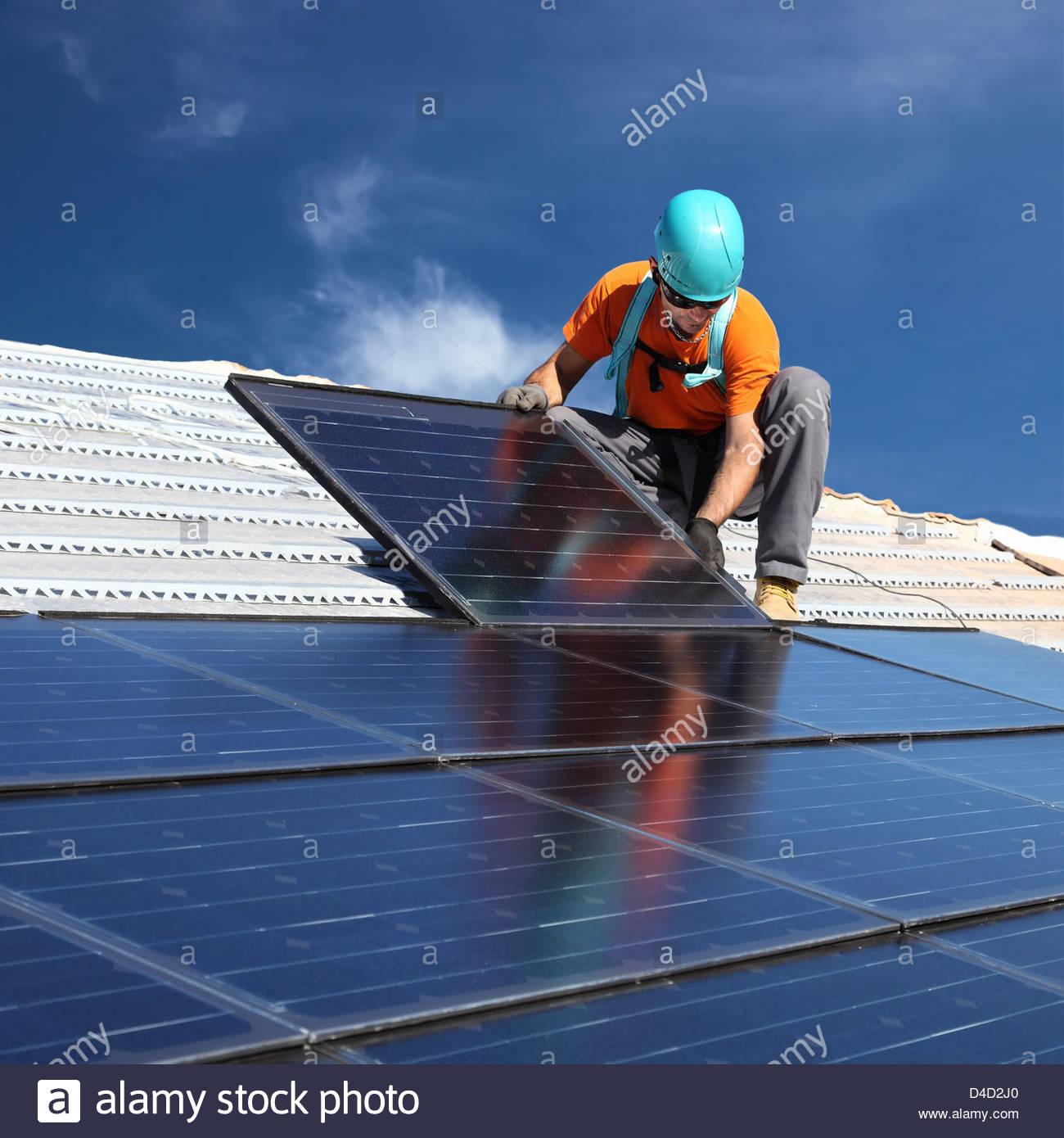 installing alternative energy photovoltaic solar panels on roof Stock Photo