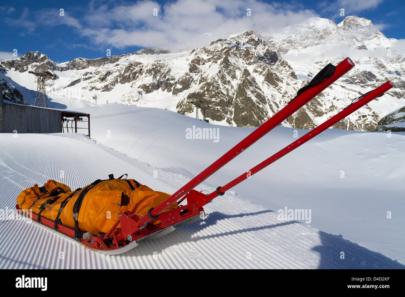 Empty mountain rescue sled over snow on mountain - Stock Image
