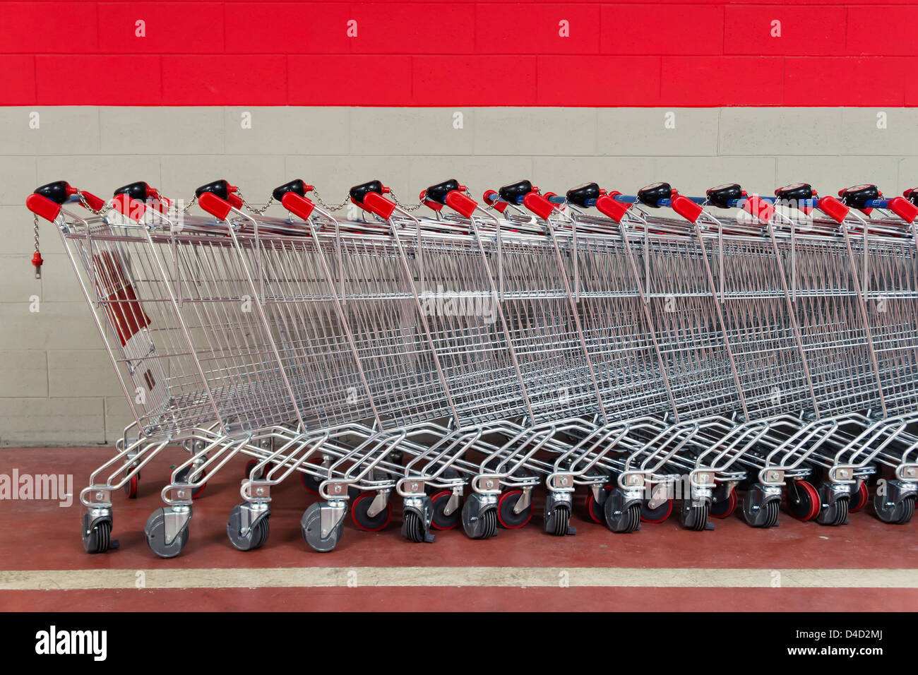 row of shopping trolleys or carts in supermarket - Stock Image