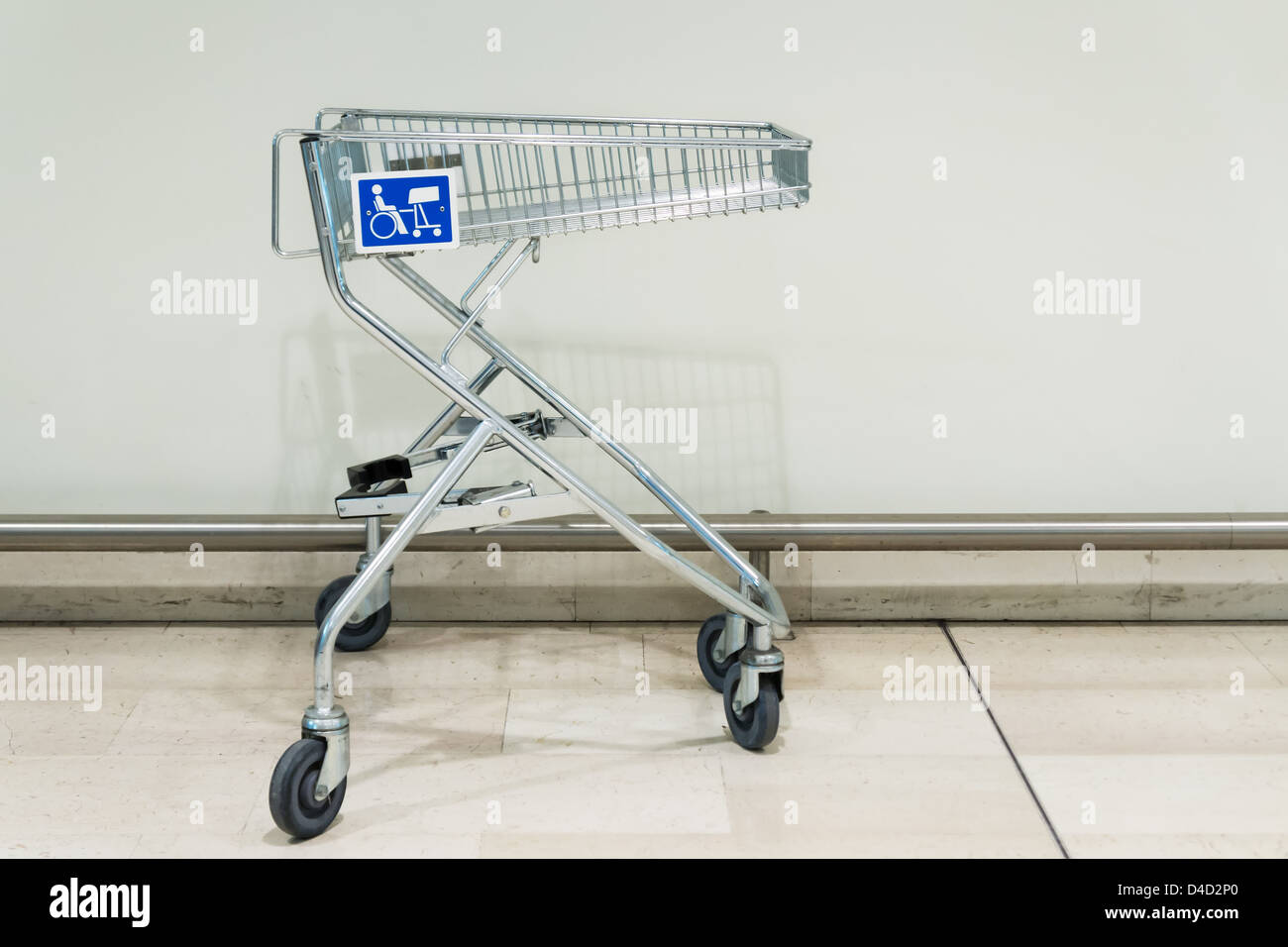 shopping trolley in supermarket with blue disabled sign - Stock Image