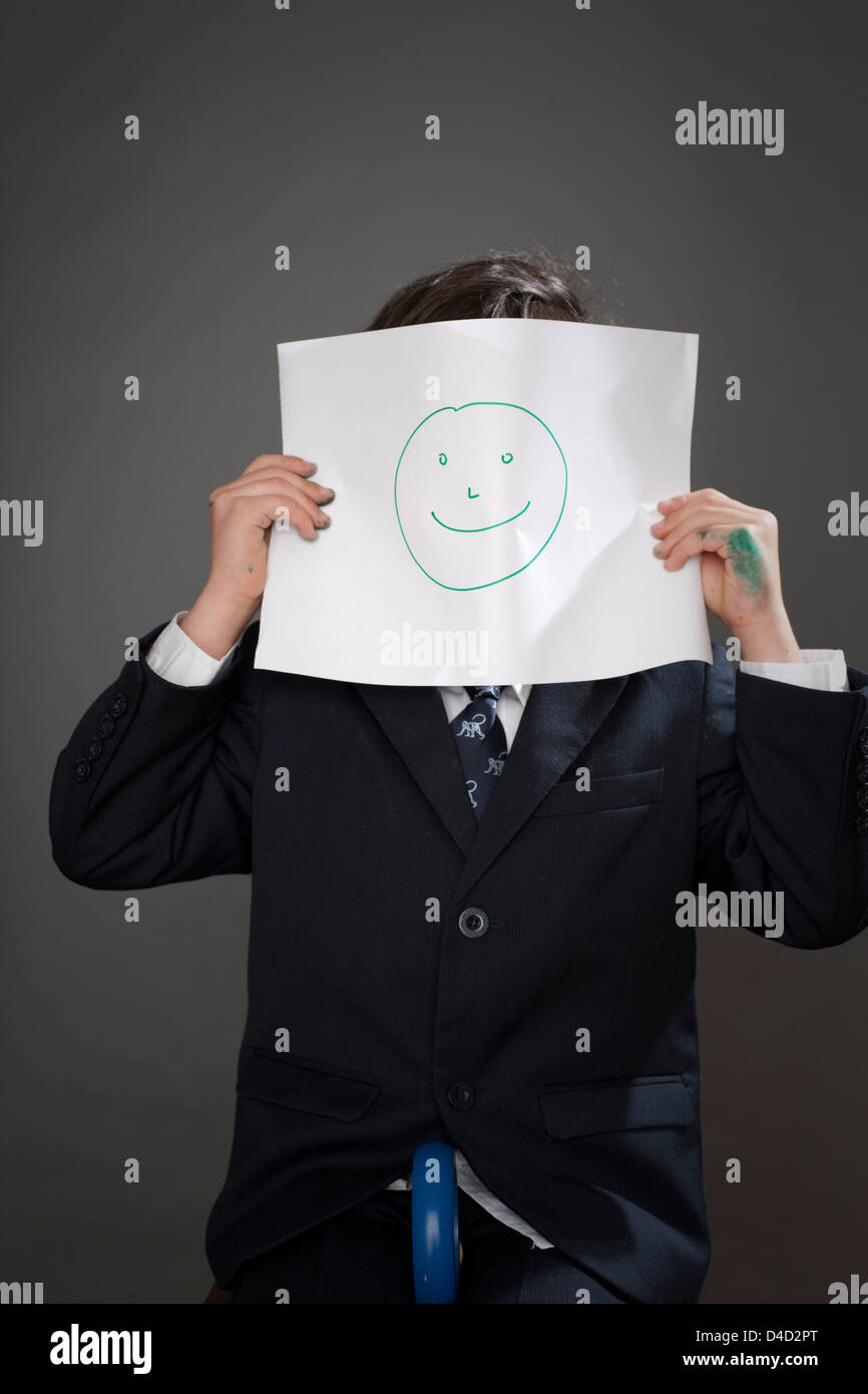 Boy covering face with drawing of happy face - Stock Image