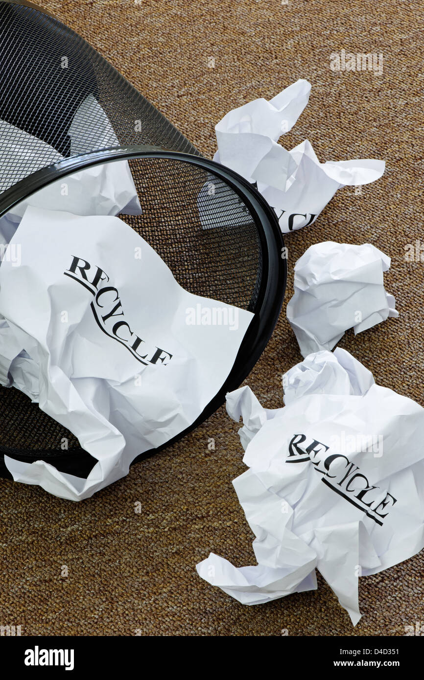 Waste paper basket with crumpled paper and the word 'recycle'. - Stock Image
