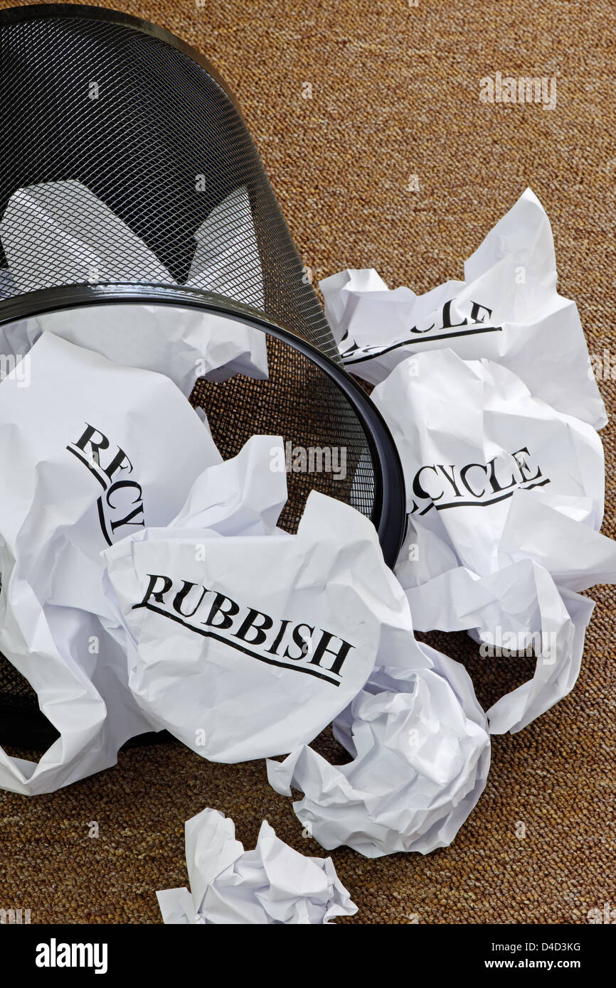Waste paper basket with crumpled paper and the words 'recycle' and 'rubbish' - Stock Image