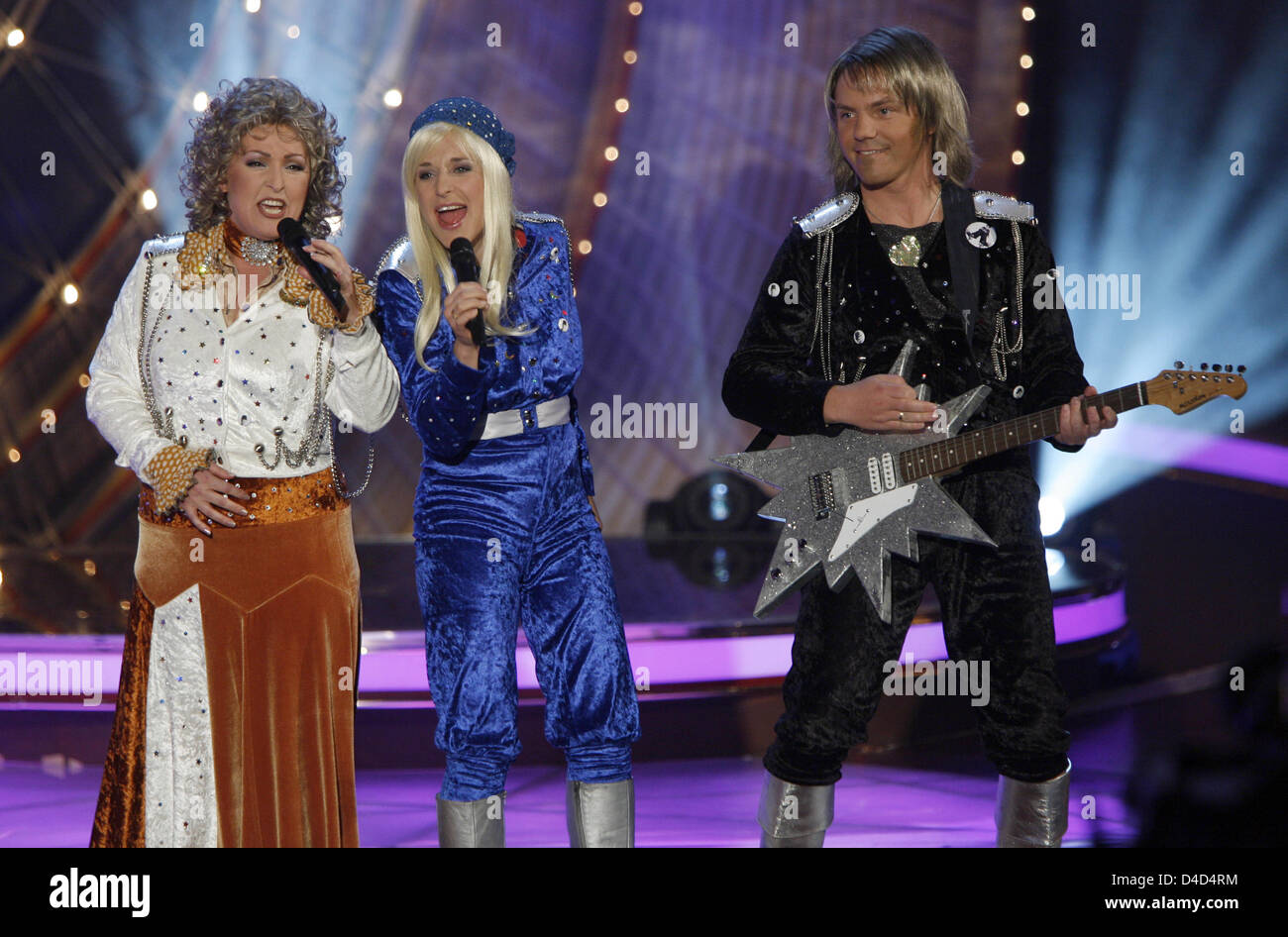 Dressed as the music group Abba Ute Freudenberg (L-R) performs with Stefanie Hertel and her husband Stefan Mross - Stock Image