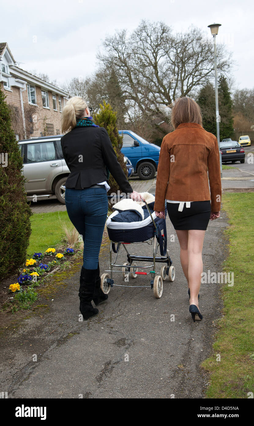 Woman pushing pram. Older and younger mothers - Stock Image
