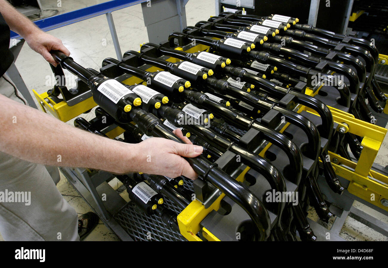 An employee of powertrain and suspension components producer ZF Sachs aligns active anti-roll bars at the plant - Stock Image