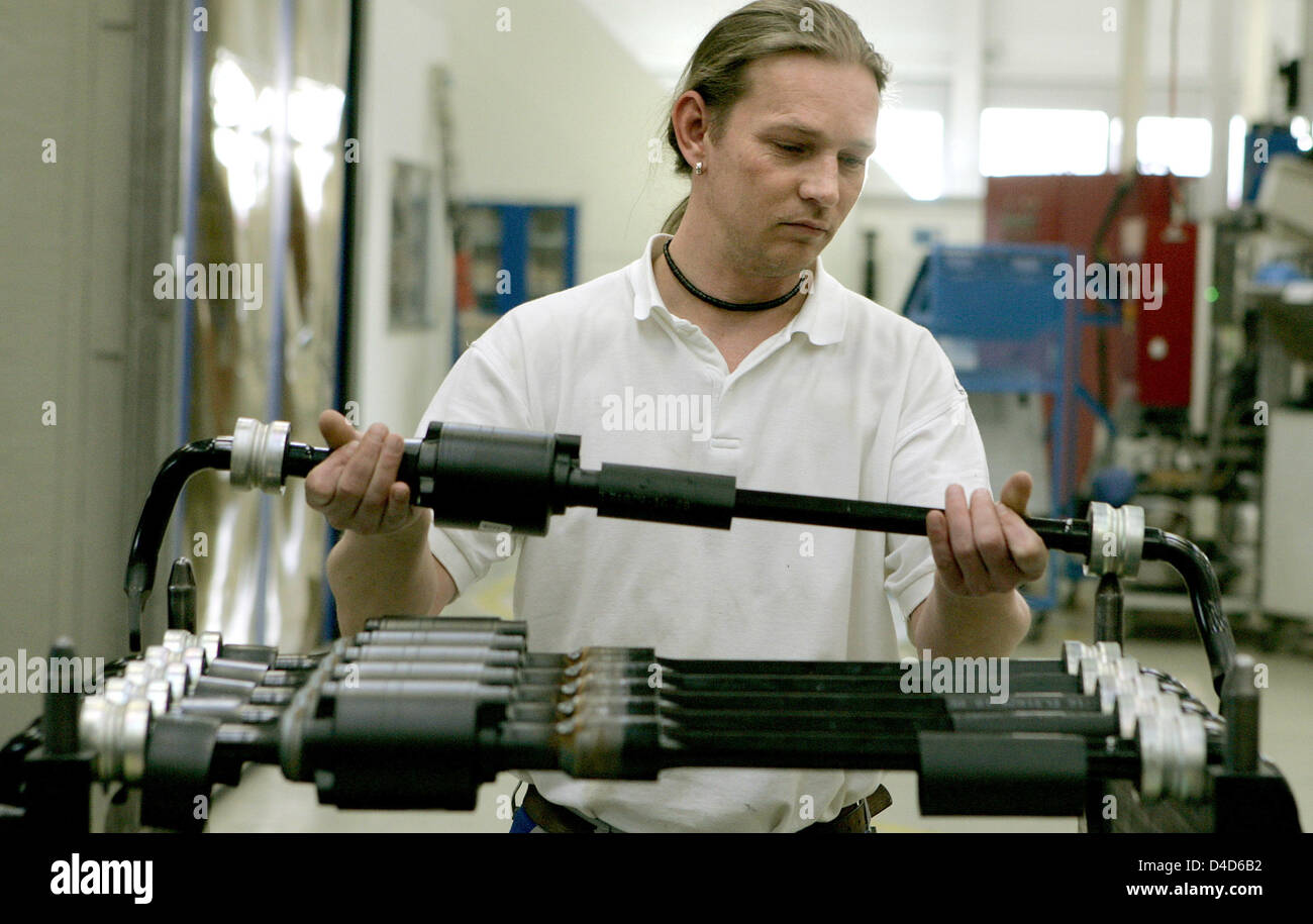 An employee of powertrain and suspension components producer ZF Sachs checks an active anti-roll bars at the plant - Stock Image