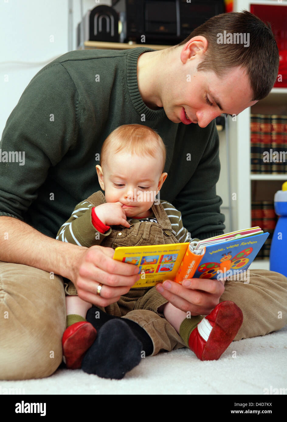 Bjoern Gerth looks through a childrens book with his son at his home in Mainz, Germany, 20 March 2008. The 29-yea - Stock Image