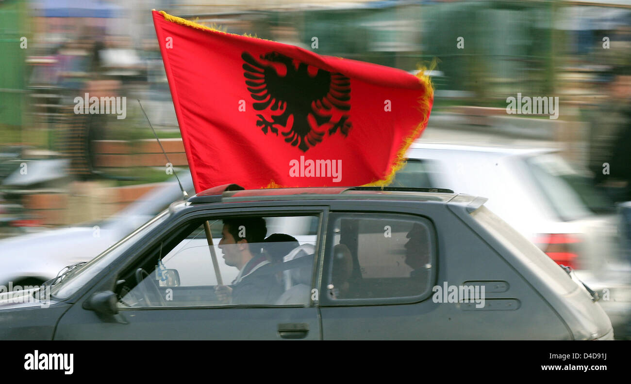 Kosovo-Albanians wave their flags celebrating the acquittal for former Kosovo prime minister and rebel commander Stock Photo