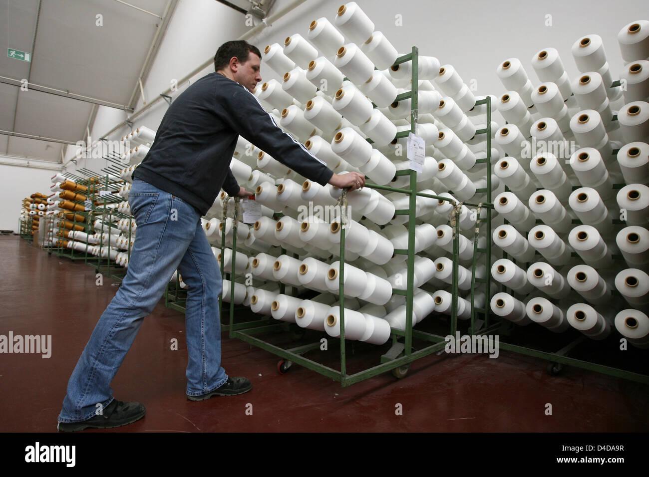 Machine operator Bernhard Olberding is pushing a wagon of bobbin cores in a factory building of the ADO Gardinenwerke - Stock Image