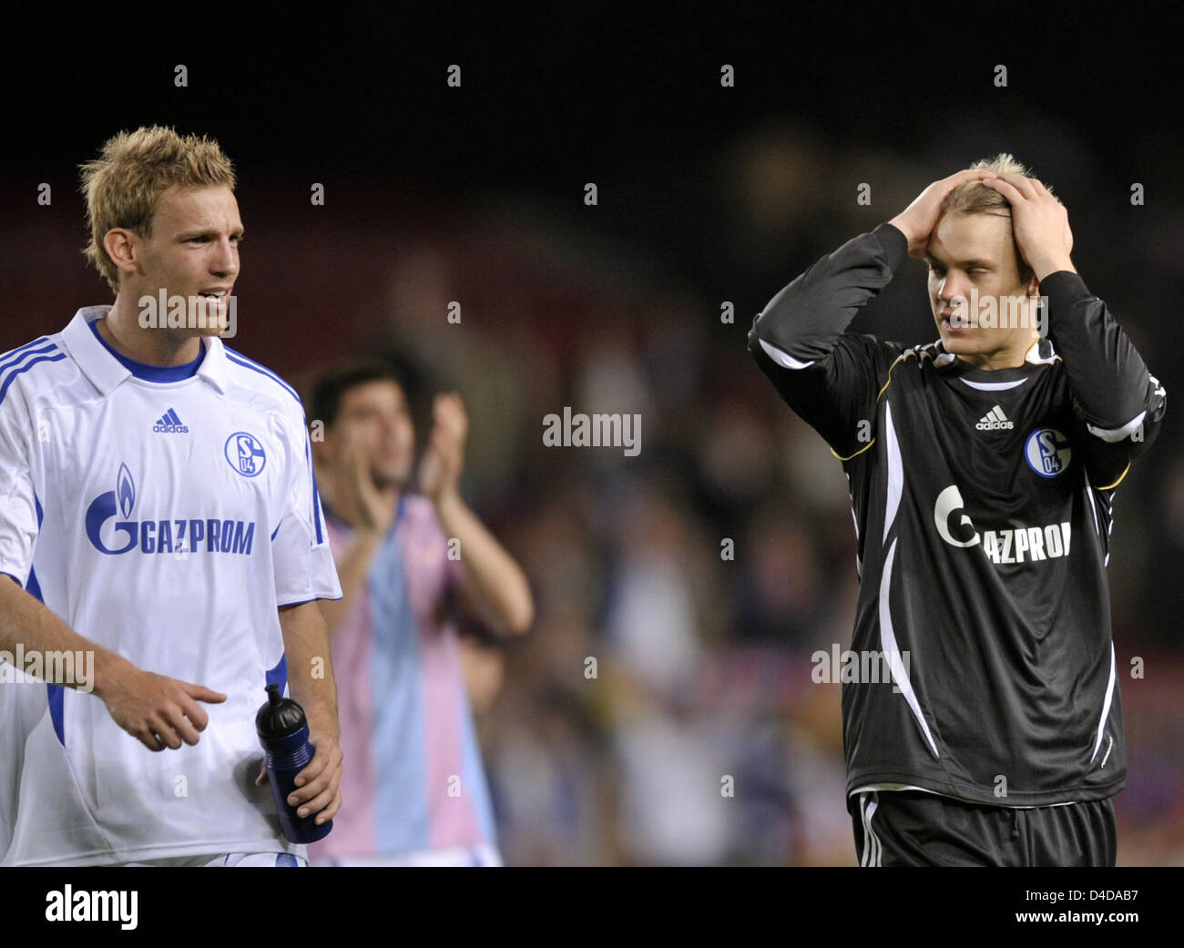Schalke's Soerne Larsen (L) and Manuel Neuer (R) leave the pitch after the UEFA Champions League quarter-finals - Stock Image