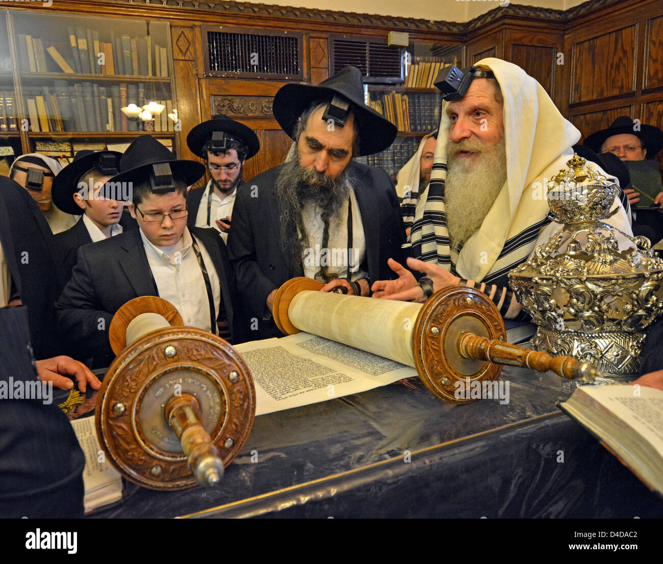 Religious Jews pray in the Rebbe's study at Lubavitch Headquarters in Brooklyn, New York. Bar Mitzvah boy blesses - Stock Image