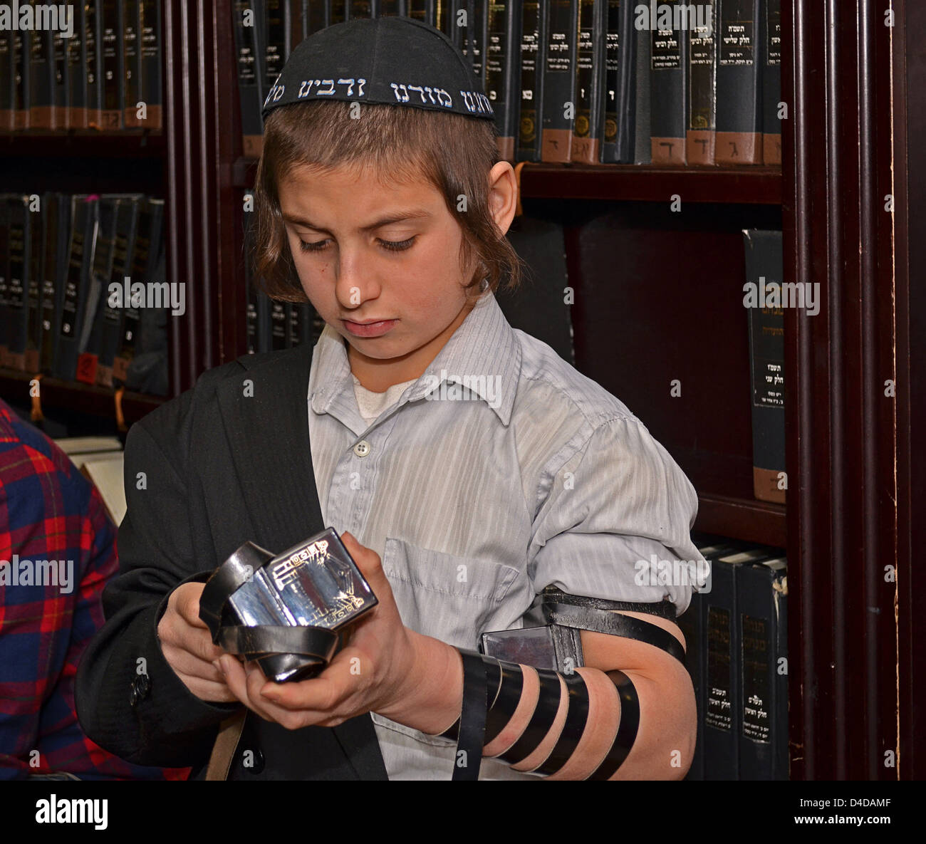1Religious Jewish boy age 12 years and 10 months prepares for bar mitzvah and putting on Teffilin - Stock Image