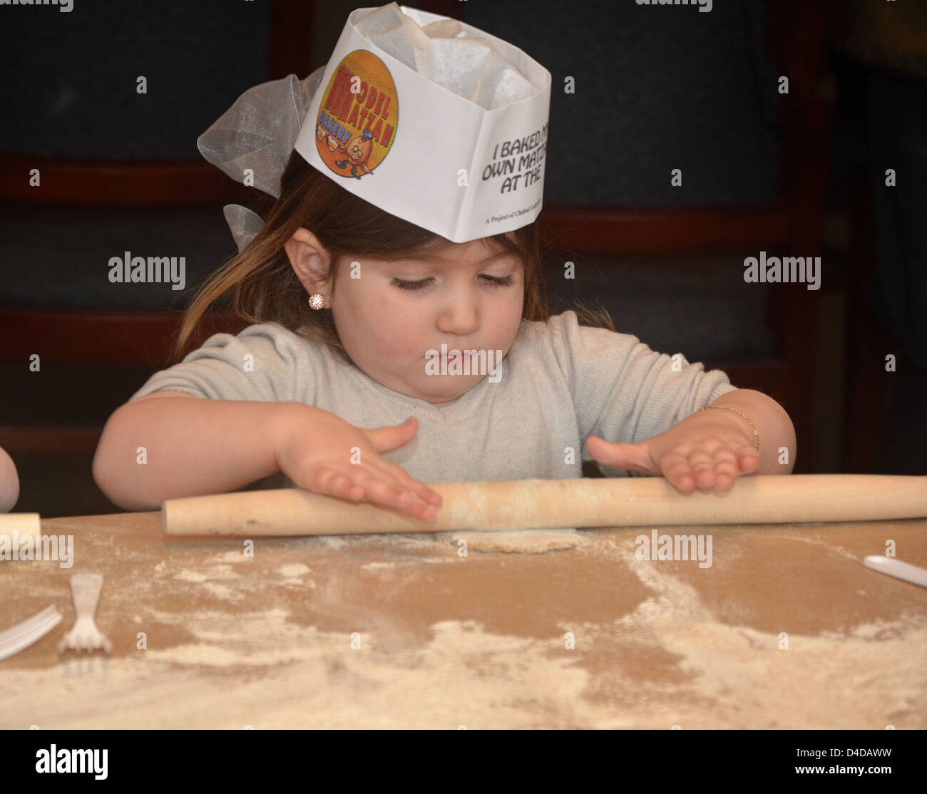 5 year old religious Jewish girl learns about Passover by baking Matzah at the Model Matzah Bakery in Brooklyn, - Stock Image