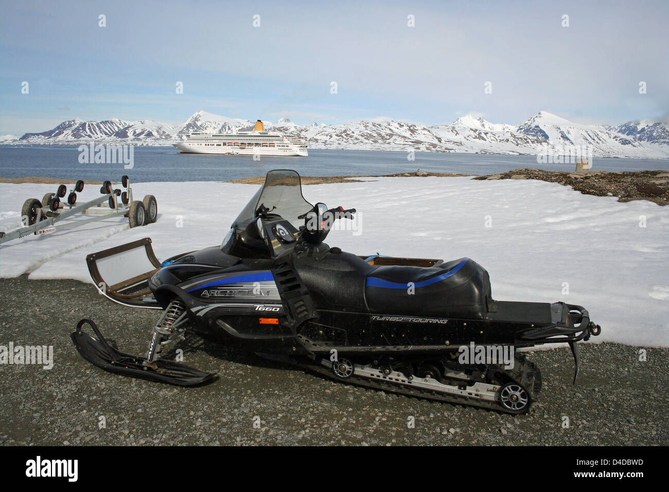 A snowmobile parked in the settlement of Ny Alesund, Spitzbergen, with the cruise liner Aurora anchored in the background. - Stock Image