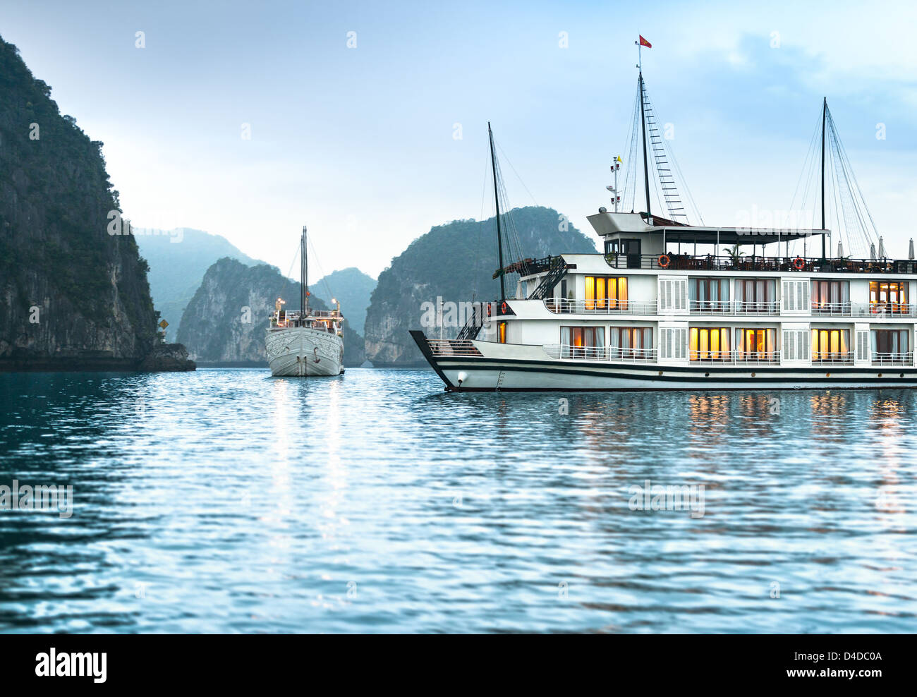 Beautiful nature in Halong bay, Vietnam, Asia. Picturesque scene with blue sky, ripple on water and mountains. Houseboat - Stock Image