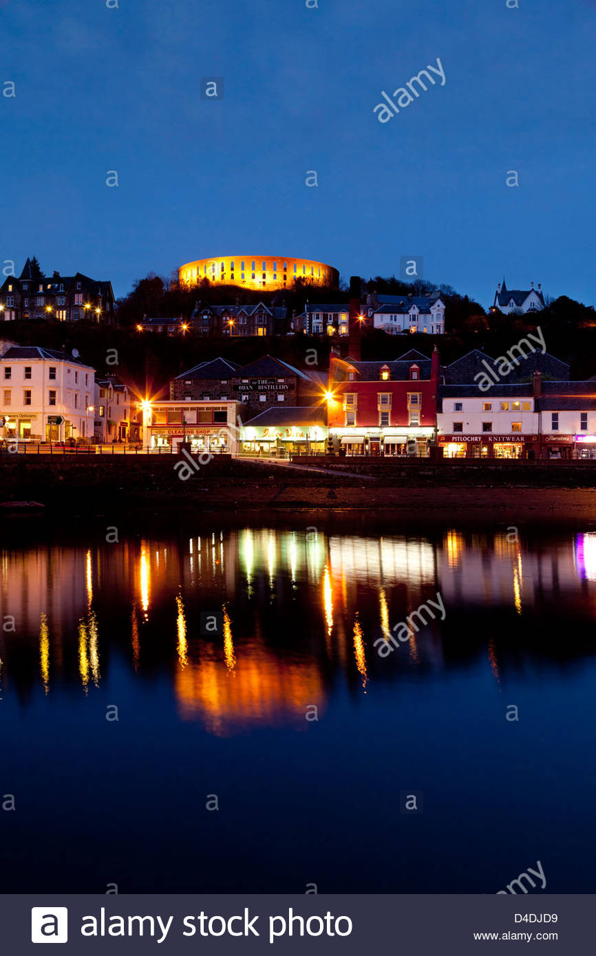 A view across the bay of Oban at dusk with McCaig's Tower prominent on the hill overlooking the town. Argyll, Scotland Stock Photo