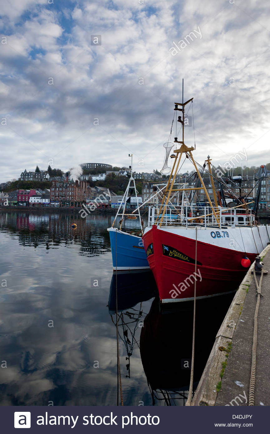 A view across the harbour at Oban with McCaig's Tower visible overlooking the town. - Stock Image