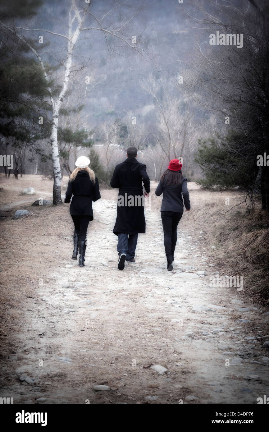 One Man And Two Women Running Through A Forest Stock Photo