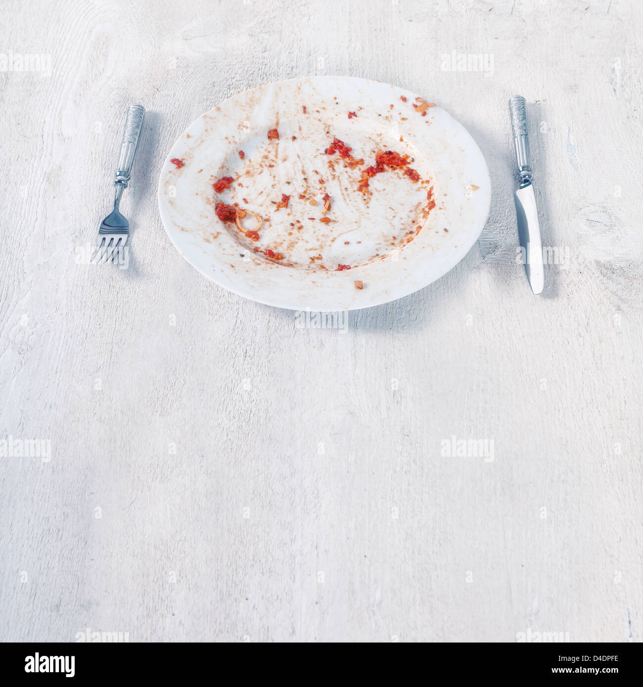 a finished plate with leftovers of tomatoe sauce and pasta - Stock Image