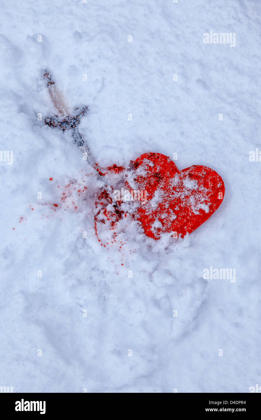 a snow-covered heart with a dagger and blood - Stock Image