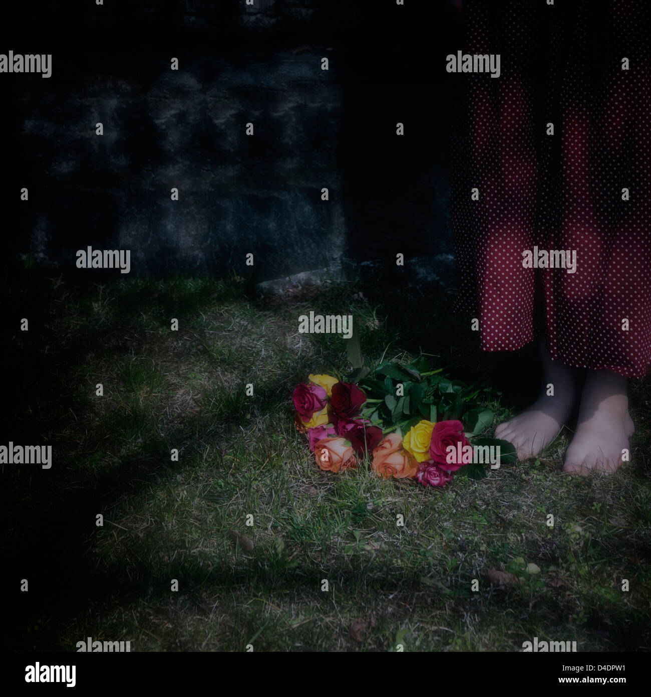 a girl in the dark, bare footed by a bouquet of flowers - Stock Image