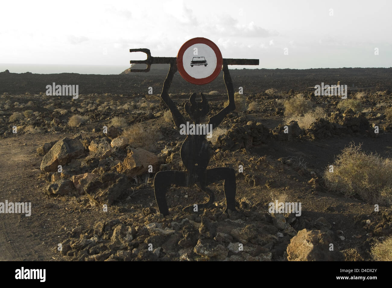 (dpa file) - A stylised devil holds a 'no entry for cars' sign at one of the entrances to Timanfaya National - Stock Image