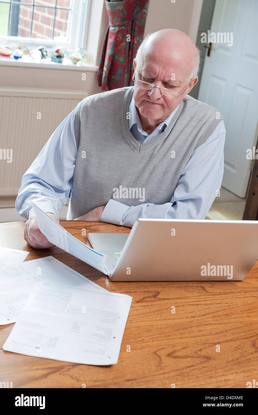 Senior man looking at bills at home with laptop - Stock Image