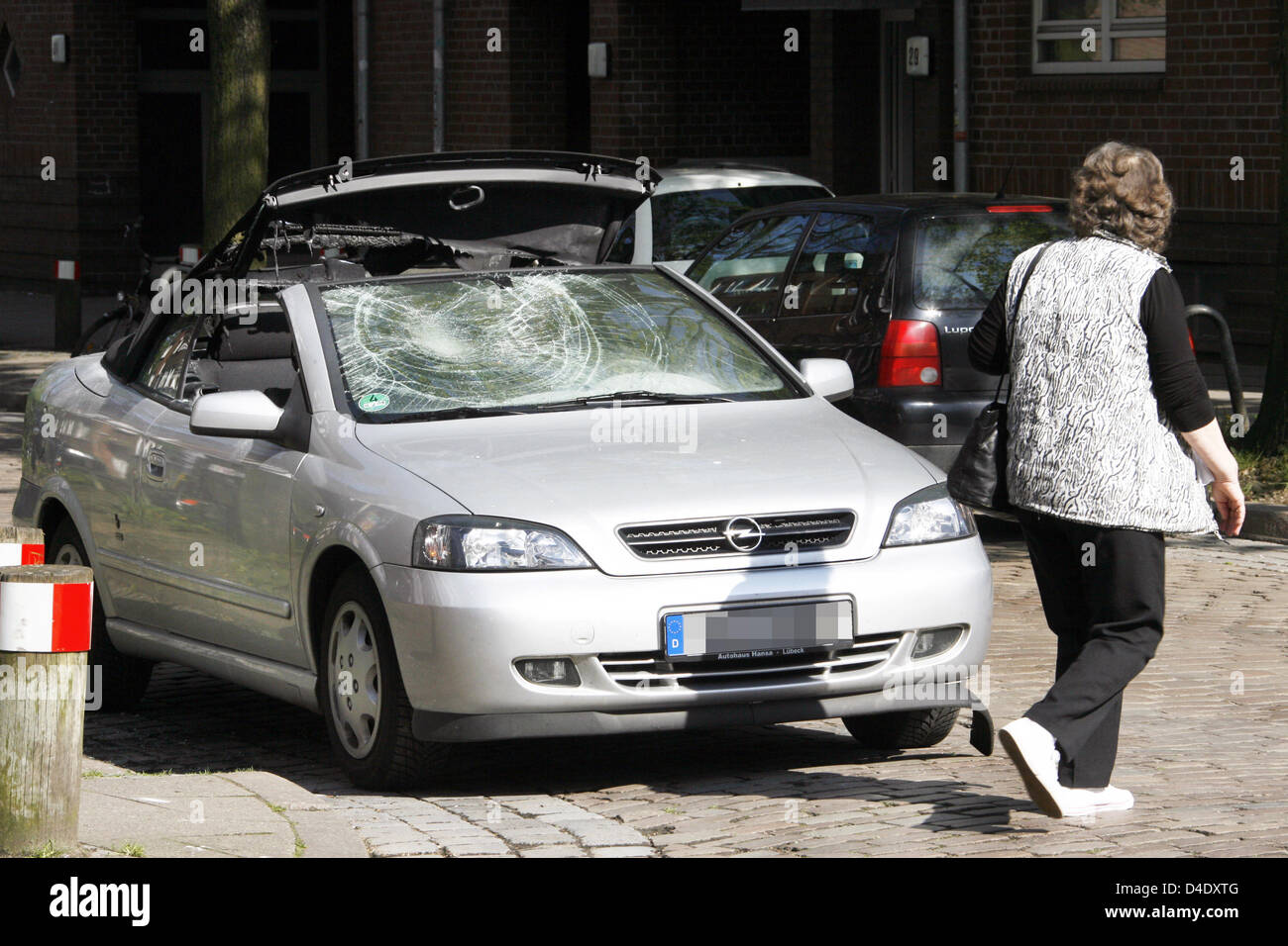 A passerby is pictured next to a damaged car after May 1st demonstrations in Hamburg, Germany, 2 May 2008. Violent Stock Photo