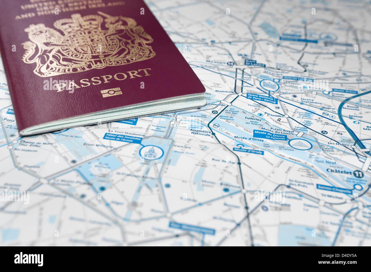 British passport on a city map of Paris, Europe - Stock Image