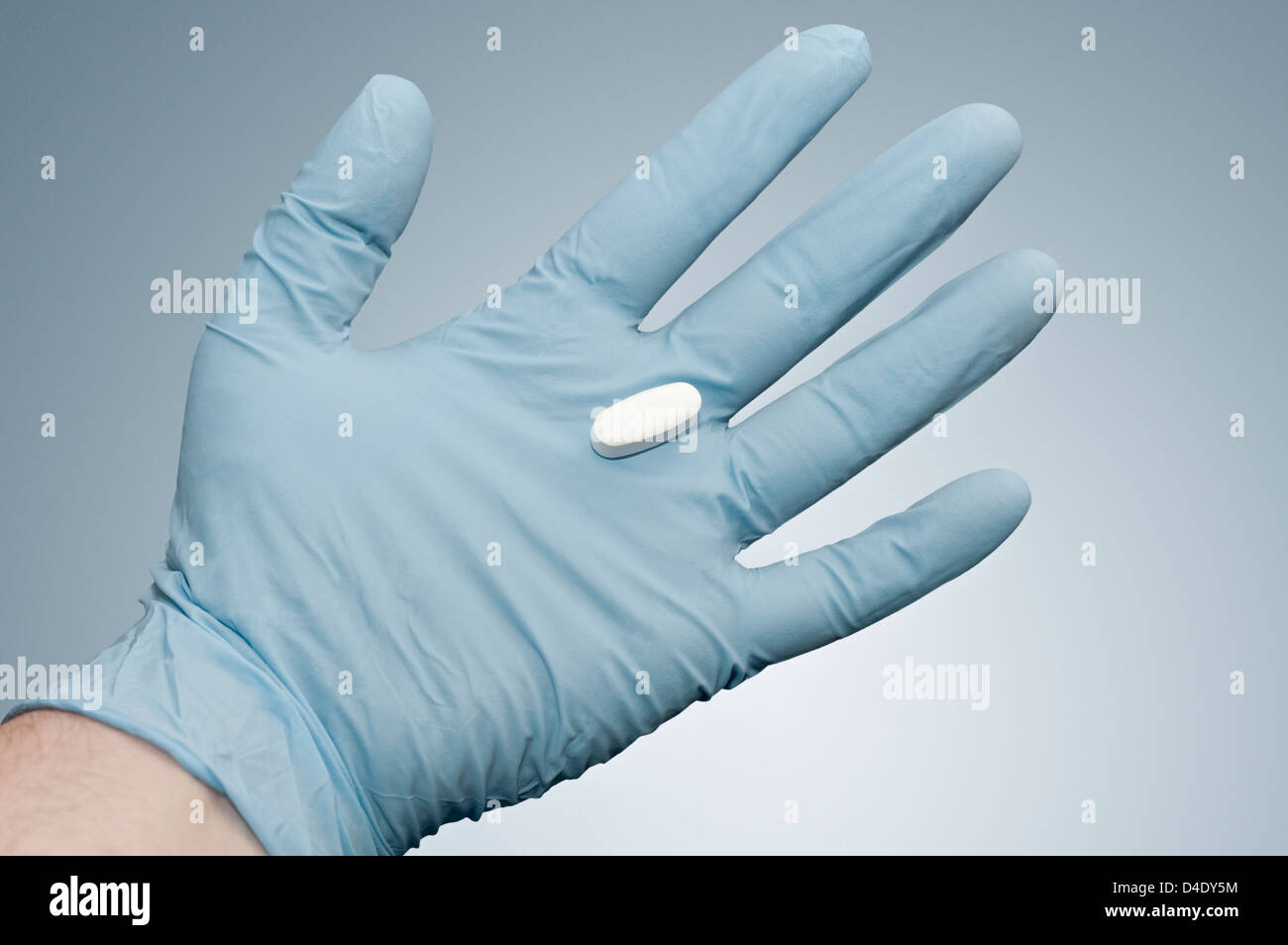 Pill on the hand of a person wearing surgical gloves - Stock Image