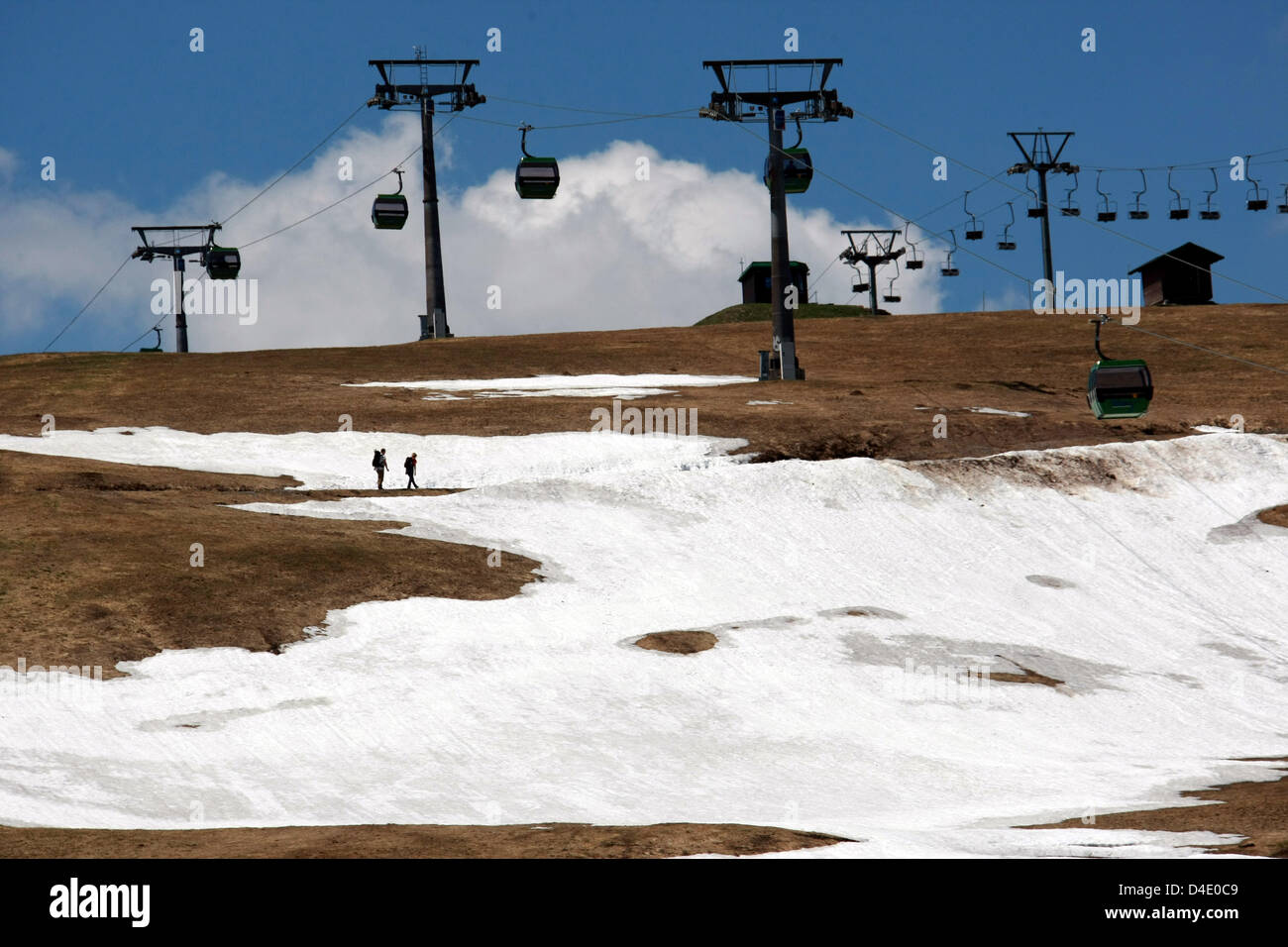 Two hikers walk on the last rests of snow on Feldberg mountain in the Balck Forest, Germany, 10 May 2008. Meteorologists - Stock Image