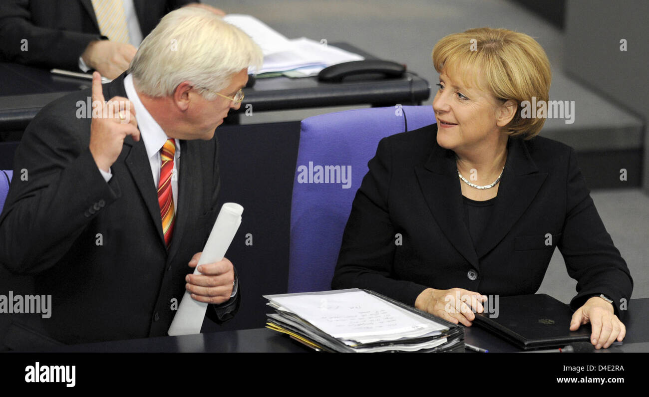 German Foreign Minister Frank-Walter Steinmeier (L) and Chancellor Angela Merkel talk during a special hearing of the German Bundestag in Berlin, Germany, 07 October 2008. German federal cabinet has agreed on the 14-month-extention of the Afghanistan mandate and an additional deployment of 1,000 soldiers, then numbering 4,500 in total. The decision has yet to be ratified by the Ger Stock Photo