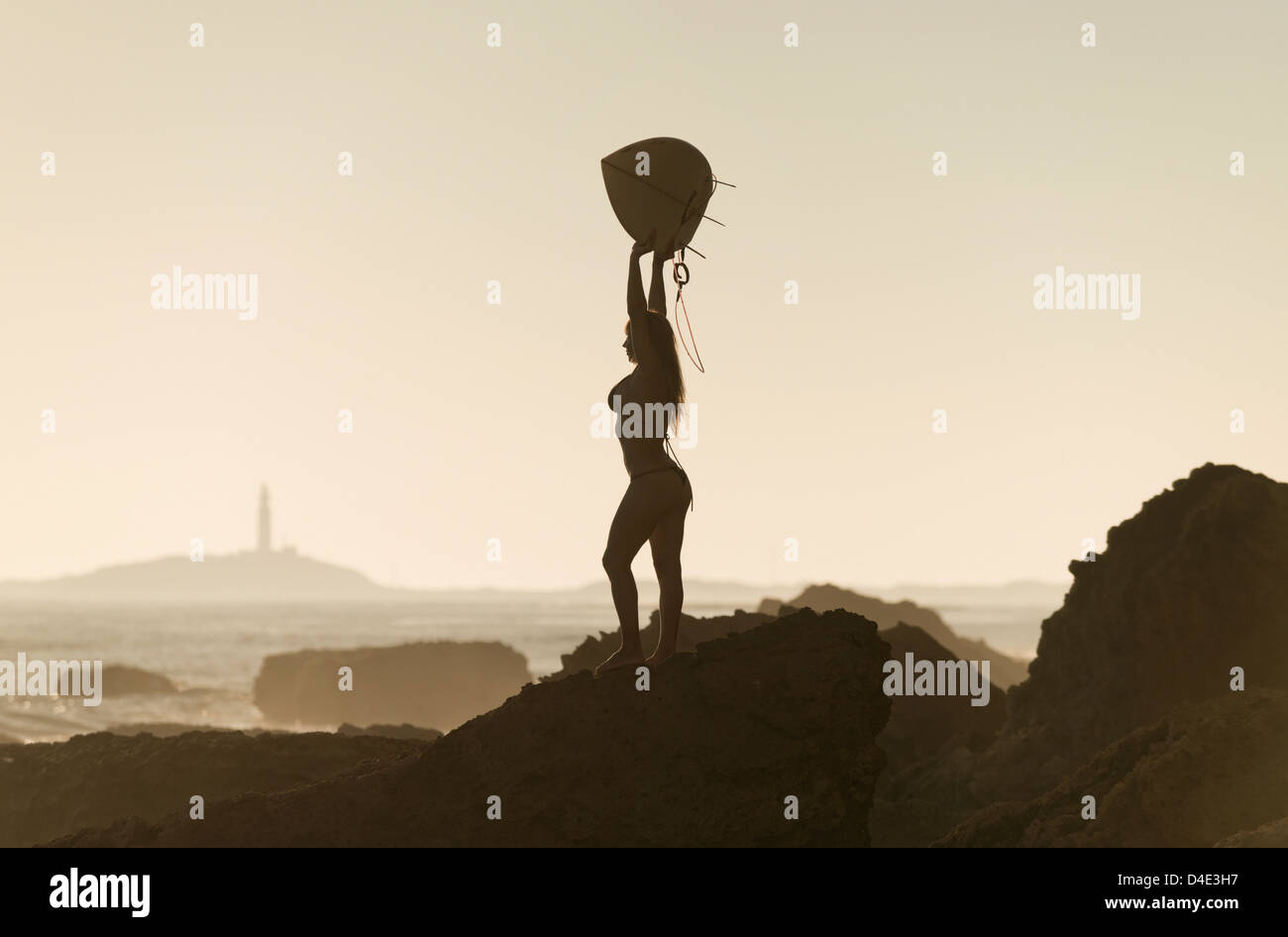 Silhouette of a female surfer holding her surfboard up above her head while standing on a rock at the coast; andalusia - Stock Image