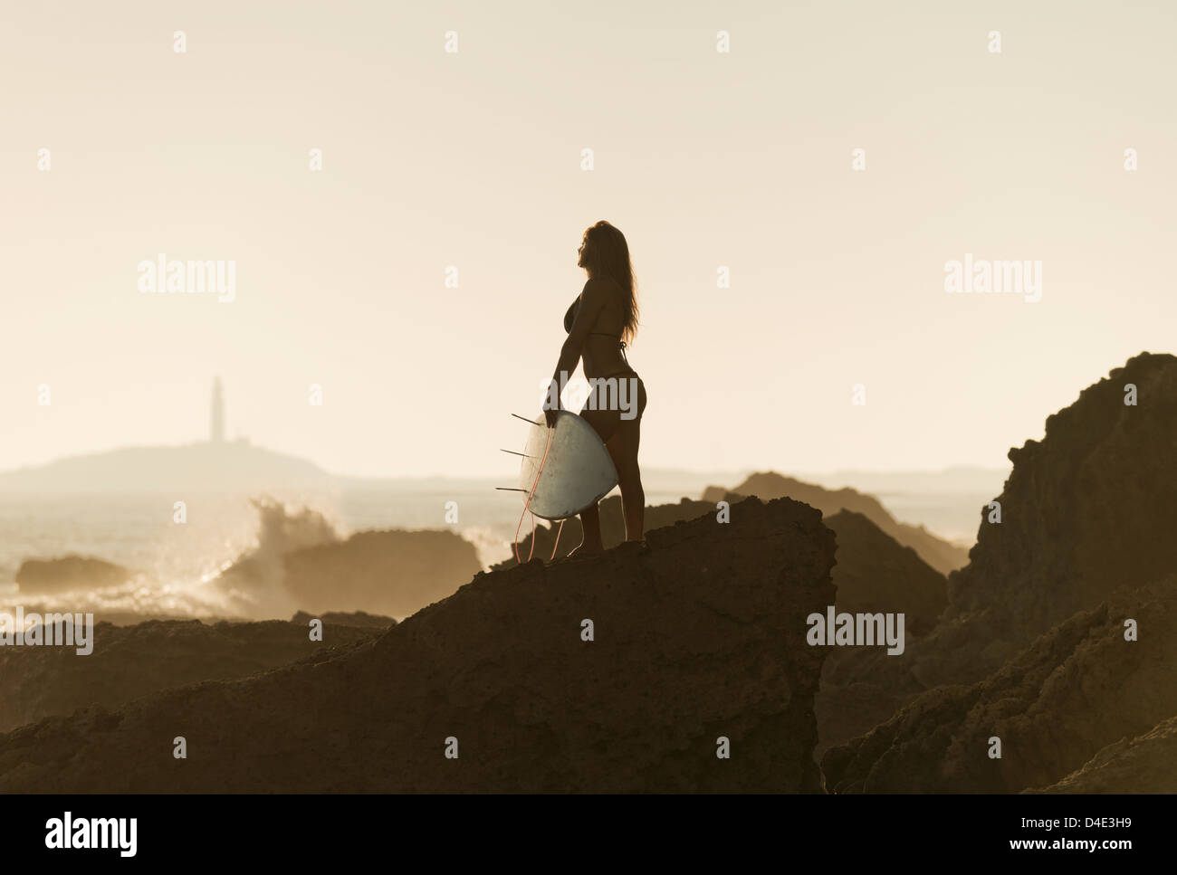 Silhouette of a female surfer holding her surfboard while standing on a rock at the coast; andalusia spain - Stock Image