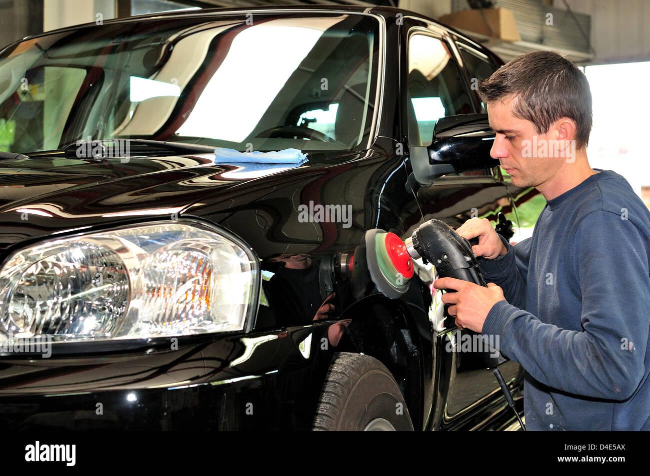 Body shop worker polishing black car. - Stock Image